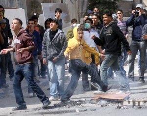 Palestyńska młodzież rzucająca kamieniami w izraelskie oddziały na punkcie wojskowym Qalndiya - zdjęcie WAFA, 16 marca 2010