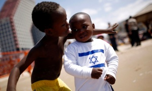 Children of migrant workers play on a beach in Tel Aviv, on Israel's 65th Independence Day