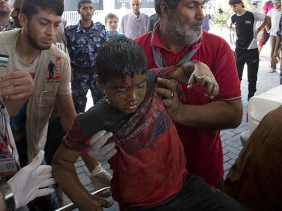 Horror toll ... a wounded child is taken in to Gaza City's al-Shifa hospital following an Israeli military strike near his family hom