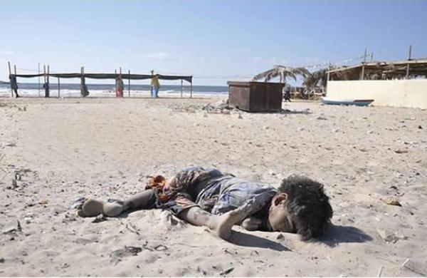 One of the four boys laying dead on a beach after coming under attack from an Israeli warship in Gaza on 16 July 2014