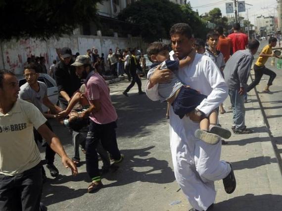 Palestyńczycy niosą rannych w izraelskim ostrzale szkoły ONZ w Rafah